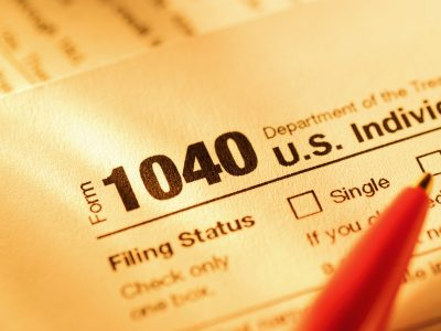 Form 1040 with red pen for US tax declaration