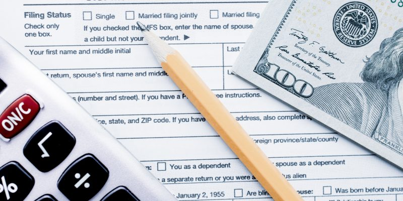 U.S. Individual Income Tax Return with a calcultator, cash money $100 dollar bills with a pencil